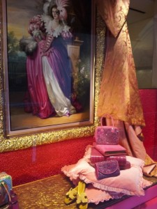 Hermes Paris. Exotic window display of pink reptile handbags and notebooks.